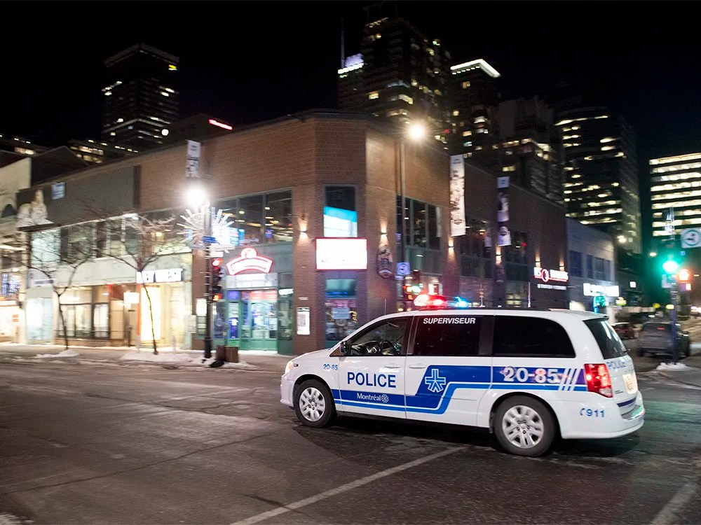 A police cruiser patrols Sainte-Catherine street in Montreal on Saturday, Jan. 9, 2021, as the COVID-19 pandemic continues in Canada and around the world. The Quebec government has imposed a curfew to help stop the spread of COVID-19.