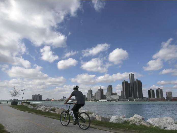 A cyclist is shown along the Detroit River in Windsor, Ontario as the Detroit, Michigan skyline is shown in the background on Wednesday, October 13, 2021.