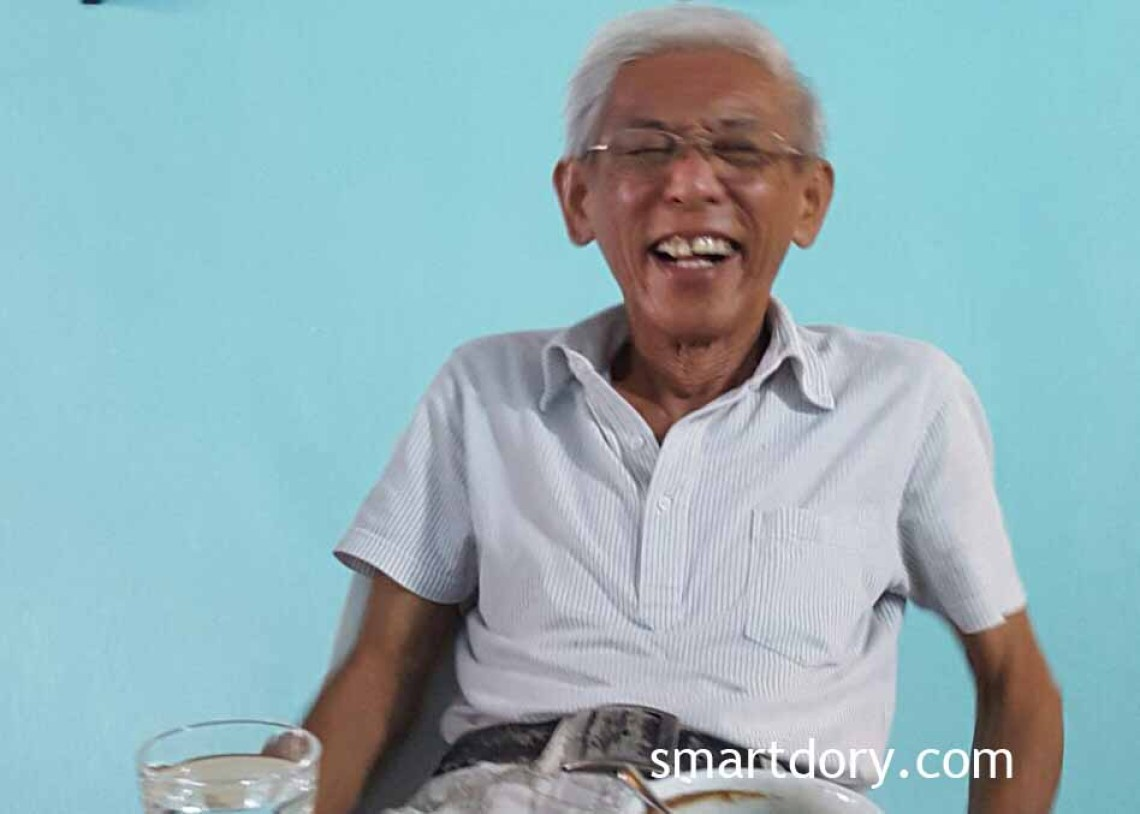 Photo shows an elderly man with glasses, sitting down and laughing. Man is identified as Frankie Cheah