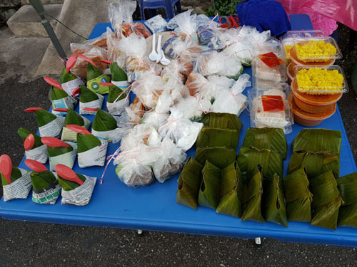 Traditional Malaysian kuih for sale on a plastic table.