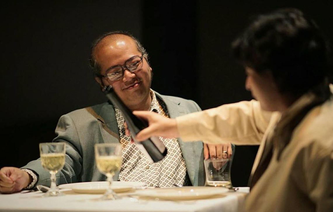 "Actor Omar Ali enjoys his dinner as Razif Hashim pours a glass of wine for him in the play ""Betrayal"" written Harold Pinter and staged at Penangpac, Straits Quay, George Town, Penang."