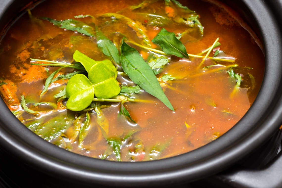 Photo shows a black clay pot with green herb leaves floating above a red tamarind based Nyonya fish soup.