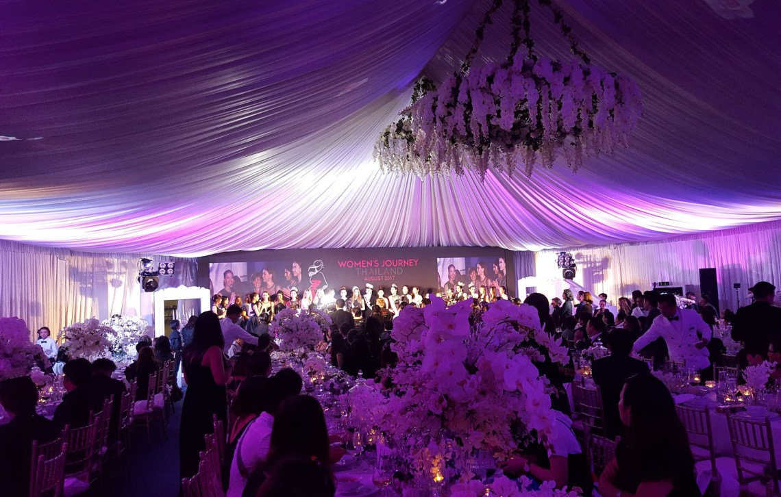 Photo shows the beautiful flower themed decorated tent with a false ceiling of billowing white taffeta which interactive projection brought to live. On stage is a line-up of women celebrities at the opening ceremony of the Women's Journey Thailand campaign 2017 on 1 August, 2017, at Nai Lert Park Heritage Home in Bangkok.