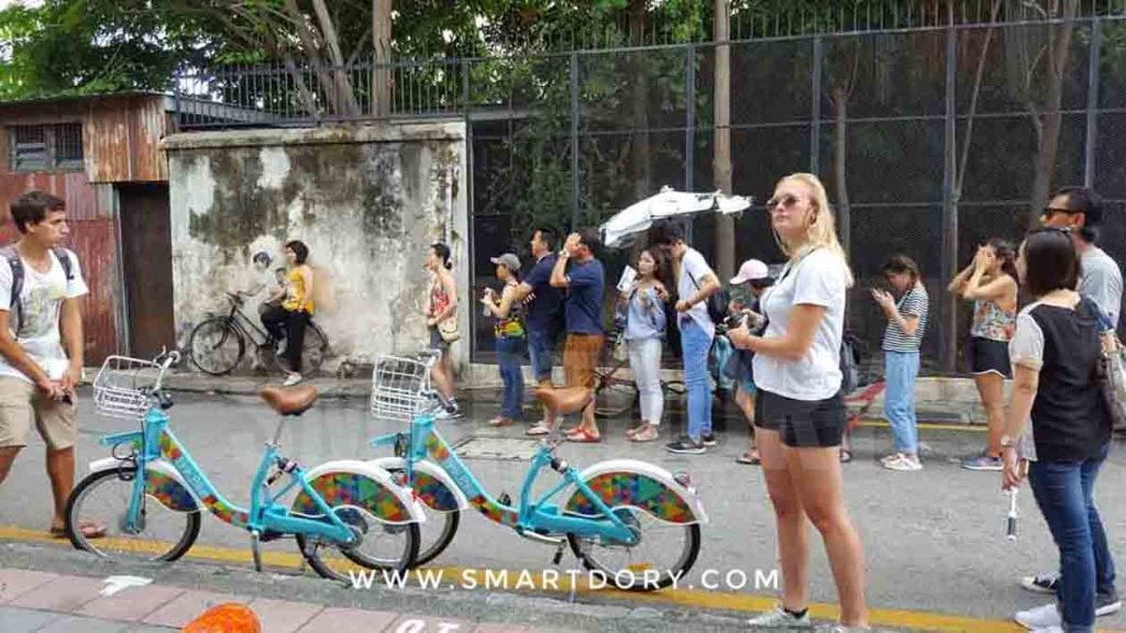 A long queue to take photos with the Children on Bicycle Mural, Armenian Street, Penang.