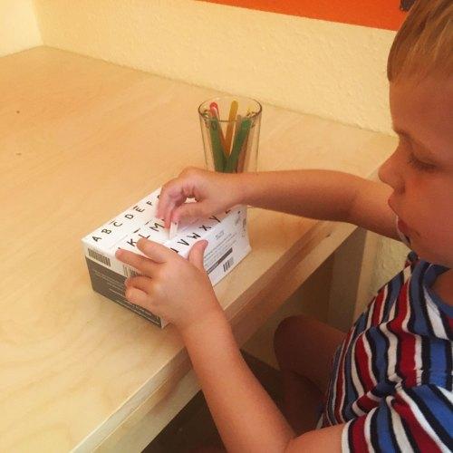 Wie Kinder lesen lernen : Kind spielt mit Buchstaben Steckspiel. Die Buchstaben sind auf Eissteilen geschrieben, die in den passend beschrifteten Schlitz in einer Pappschachtel gesteckt werden müssen. Dieses Spiel ist einer der ersten Schritte zum Buchstaben und schließlich zum Lesen lernen.