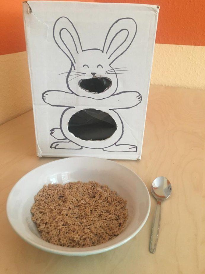 Ideen zur Beschäftigung für Kinder: Gebastelter Hase wird mit trockenen Nudeln gefüttert