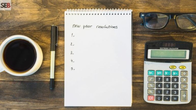 A list with new year resolution, cup of coffee, pen, specs and calculator on a wooden table