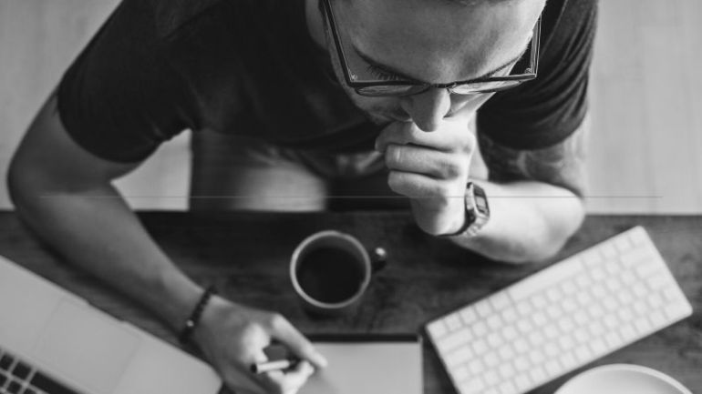 3 reasons to build your brand - a man hunched over his notepad with a cup of coffee