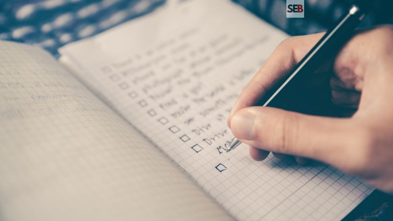 Event planning checklist -hand holding pen writing out to-do list