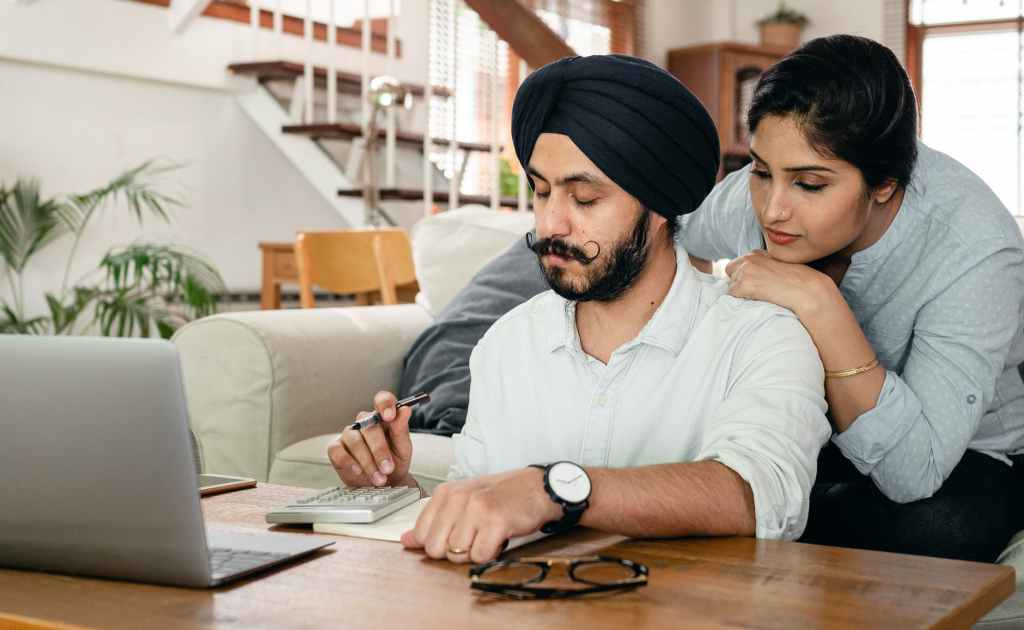 cheerful couple counting with calculator and writing notes