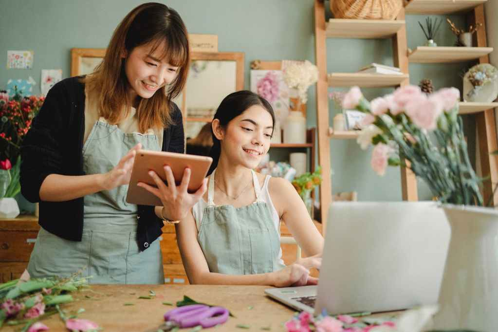 happy multiracial women working on gadgets in floral store