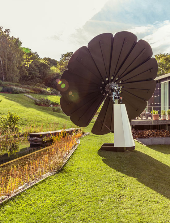 A SmartFlower Solar Panel Sits in the Yard Beside a Small Pond Between Two Houses