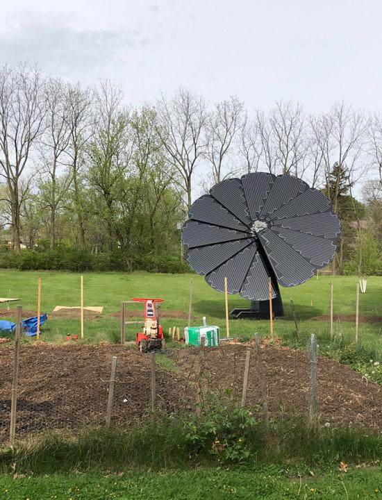 O painel solar SmartFlower tem vista para um pequeno patch de jardinagem no Centro-Oeste