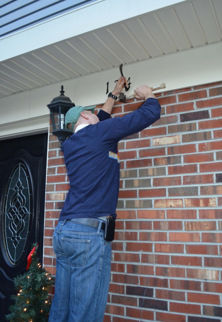 Hubby taking down house numbers