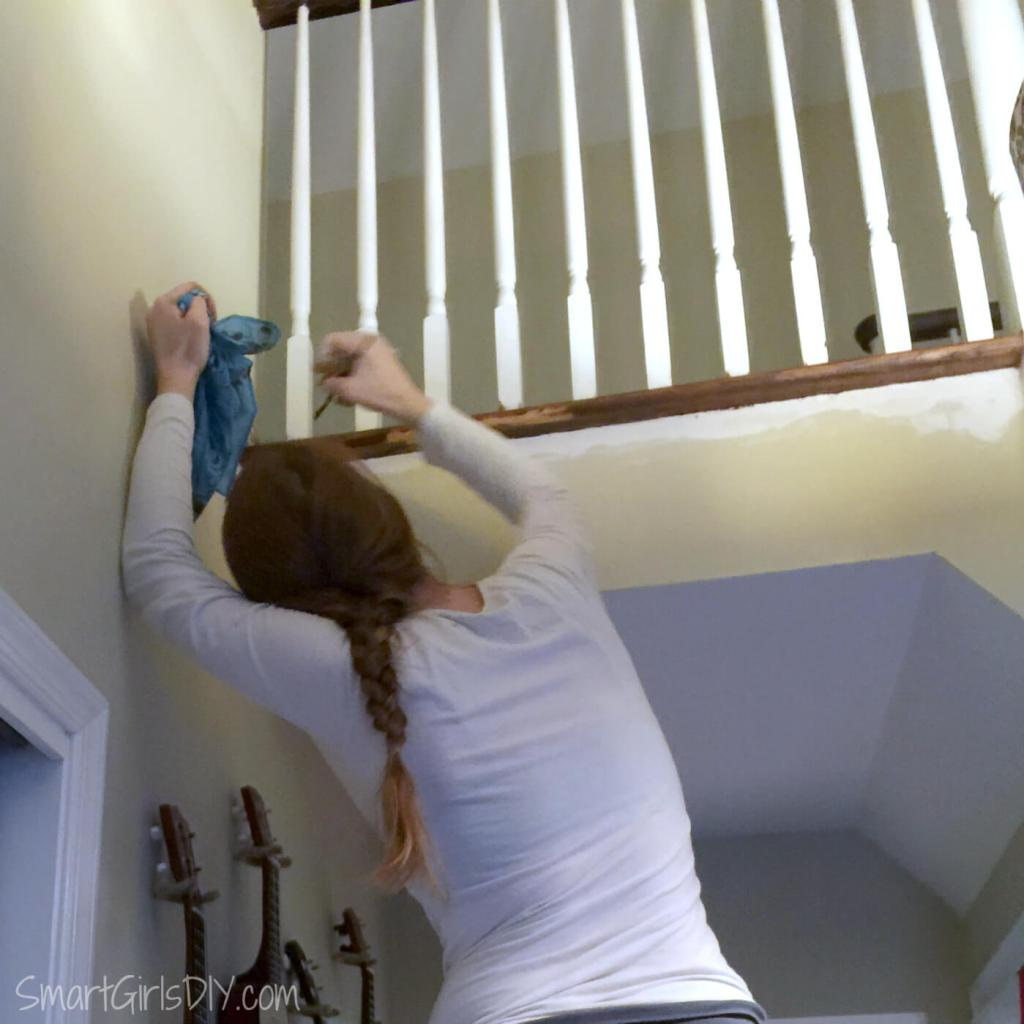 Staining wood staircase overhang with paint brush