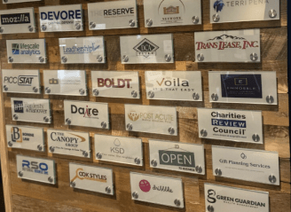 Glass nametags with the names of organizations who use the Reserve coworking space on a wooden wall at the Reserve, a coworking location in Roseville, Minnesota