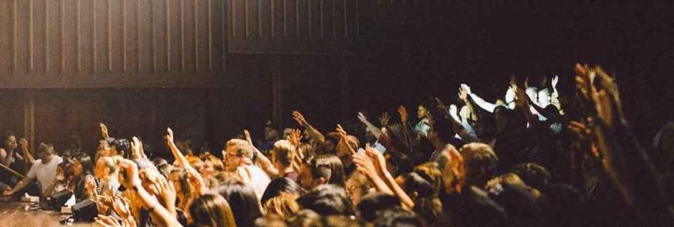 Students Raisin Hand in Large Auditorium