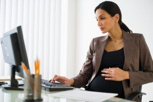 Pregnant businesswoman working on computer. Image shot 2010. Exact date unknown.