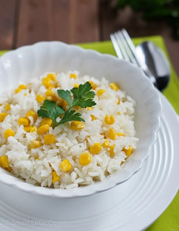 Rice with Corn served on a white plate and topped with a parsley leaf.