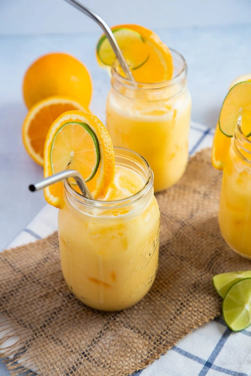 El jugo se sirve en frascos de albañil con rodajas de naranja y una pajita de metal.