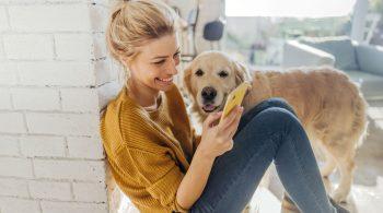 Frau mit Hund nutzt Apps