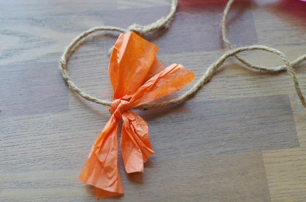 Tie tissue paper around ribbon