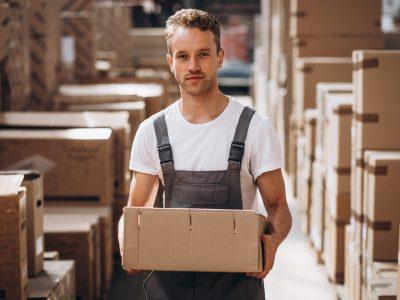 ung mand står på lageret og holder en papkasse.
