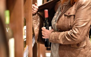 woman stealing wine at store