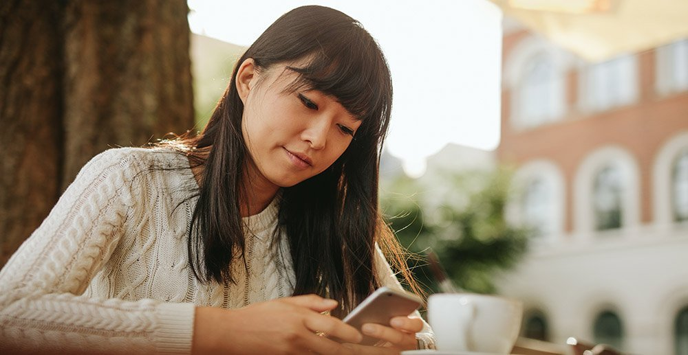 Image of young woman sitting at a table with a coffee using mobile phone text your customers