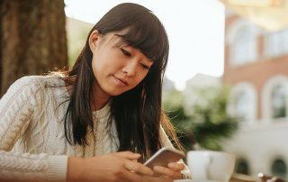 Chinese woman typing text message on smart phone in a cafe. Image of young woman sitting at a table with a coffee using mobile phone.
