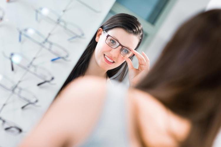 woman putting on designer frames in shreveport optometrist office