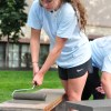 Junior Maddie Mann rolls paint onto one of the benches. Photo by Abby Hans