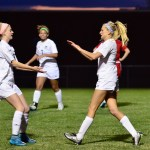 Senior Elisabeth Shook high-fives sophomore Maddy Muther after scoring a goal. Photo by Diana Percy