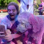 Senior Katherine Chester takes a selfie with a dog after finishing the race. Photo by Ellie Thoma