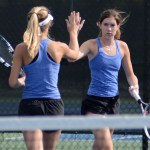 Doubles partners, Junior Caro Bush and Senior Gretchen Cooper, high five between points. Photo by Ellen Swanson