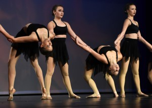 Juniors Toni Englund and Tinka McCray lean back while juniors Savannah Worthington and Katie Faught hold them up while they perform in the varsity all-junior routine. Photo by Lucy Morantz