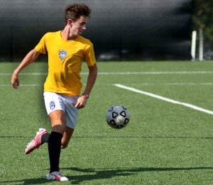 Sophomore TJ Johnson dribbles down the field. Photo by Luke Hoffman