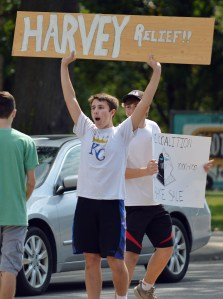 Junior Will Barreca tries to attract customers by waving a sign on Mission Road. Photo by Ally Griffith