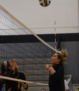 After illegally touching the net while trying to hit the ball, Senior Sydney Ashner jumps away from the net. Photo by Aislinn Menke