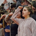 Senior Riley McCullough sings the school song with the student section at the end of the game. Photo by Ally Griffith