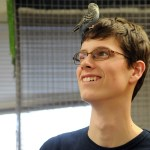 Junior Max Bare jokingly places a parakeet on his head to entertain the children. Photo by Katherine McGinness