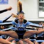 Junior Maggie Gray does a toe touch during the competition cheer performance. Photo by Izzy Zanone