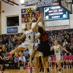 Junior Emma Eberhart and Senior Toni Englund jump up to get a rebound after North scores a point. Photo by Kathleen Deedy