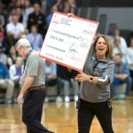 Athletic Director Gayle O'Grady proudly holds up the check donated to the Coaches vs Cancer fundrasier, where Shawnee Mission East won the competition against Rockhurst to see who could donate the most. Photo by Luke Hoffman