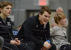 Senior Justin Schuman cheers on his teammate senior Andrew Schmidt. Photo by Katherine McGinness