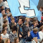 Senior Cooper McCullough runs with the E flag as the pep assembly begins. Photo by Katherine McGinness