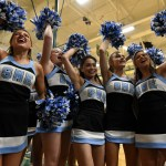Juniors Gracie Kost, Chloe Wright, and Emma Kerwin, senior Astrid Cifuentes, and sophomore Ellie Phillips jump to finish the school song with the student section. Photo by Lucy Morantz