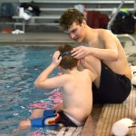 Senior Carter Kirkland helps a boy with his goggles. Photo by Luke Hoffman