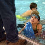 A girl participating in the Makin' Waves Swim Clinic looks up at Coach Wiley Wright. Photo by Luke Hoffman