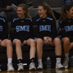 Seniors Katie Hise and Sofia Stechschulte and junior Emma Eberhart laugh with each other as the tip off starts. Photo by Morgan Plunkett